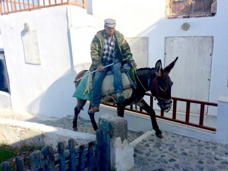 Oia donkey owner getting a ride in Santorini