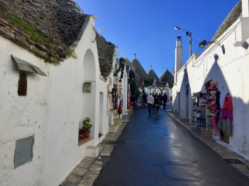 Alberobello street view - grey narrow lane with white fronted trulli shops either side. there are a few people in the street and some shops have goods hanging outside
