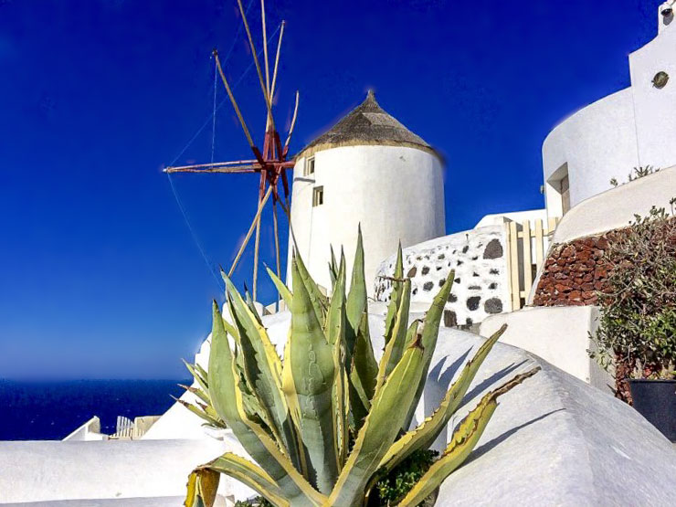 Blue and white buildings with a windmill on Santorini in winter