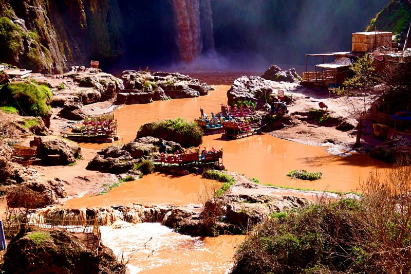 Pools of brown water at the bottom of the Ouzoud Waterfalls with three brightly coloured rafts