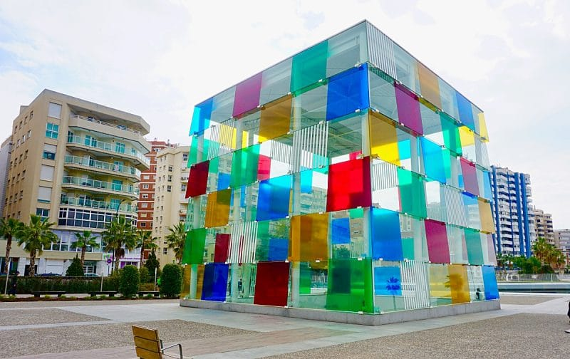 Multi-coloured squares panes of a huge glass cube sitting on one side.