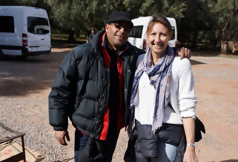Ali, man on left wearing black jacket black cap and sunglasses with arm around woman ( Michelle)with white jumoer and blue scarf