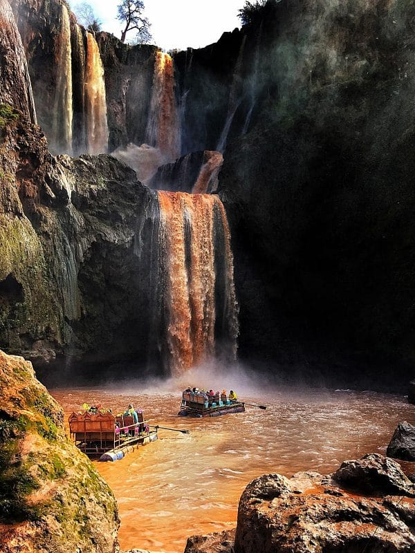 Three tiers of the Ouzoud Waterfalls- the water is brown and the overall drop is about 100metres. At the bottom are two colourful rafts with about 8 people in each with a rower at the front of each.