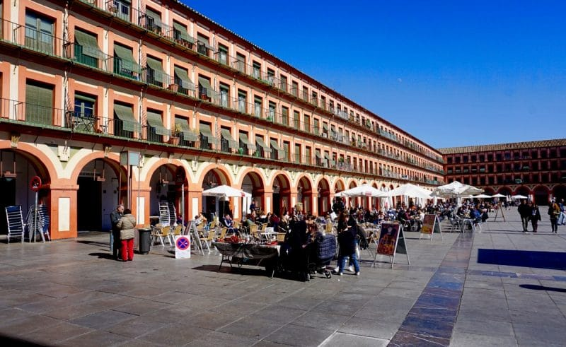 A large plaza with pink surrounding 4 story buildings containing chairs from nearby cafes