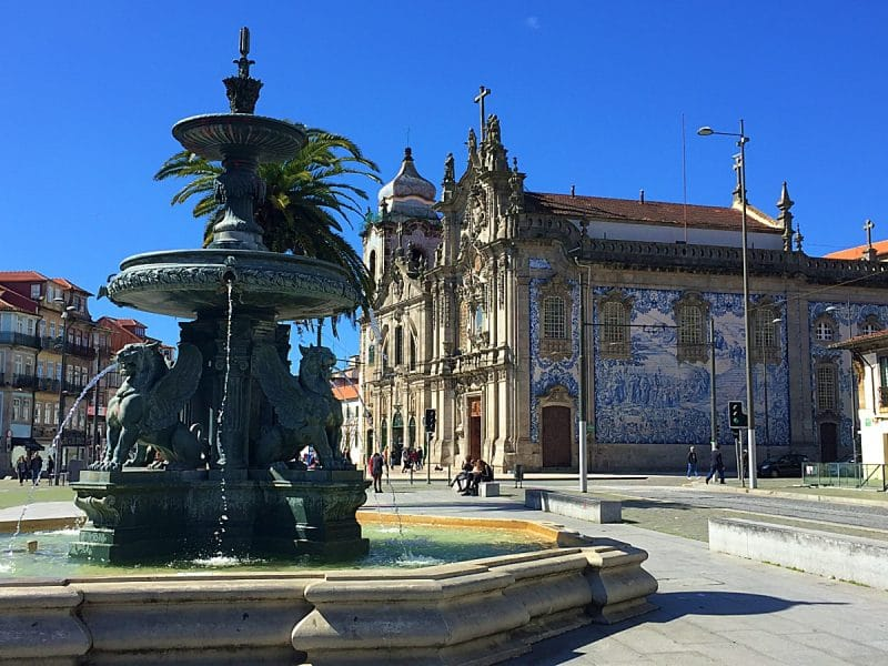 Fountain in the foreground and a blue / white tiled faced on a granite church in the background