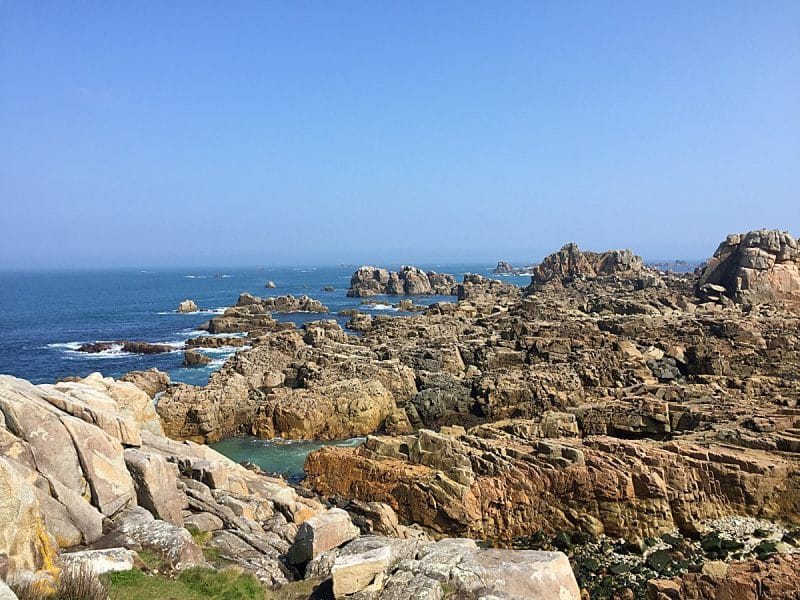 Rocky coastline with a blue sky and green tinged sea at Plougrescant, Brittany