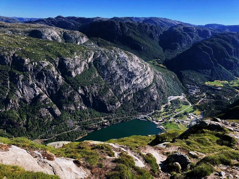 view down into the valley showing a tiny town and the harbour of the Lysefjord
