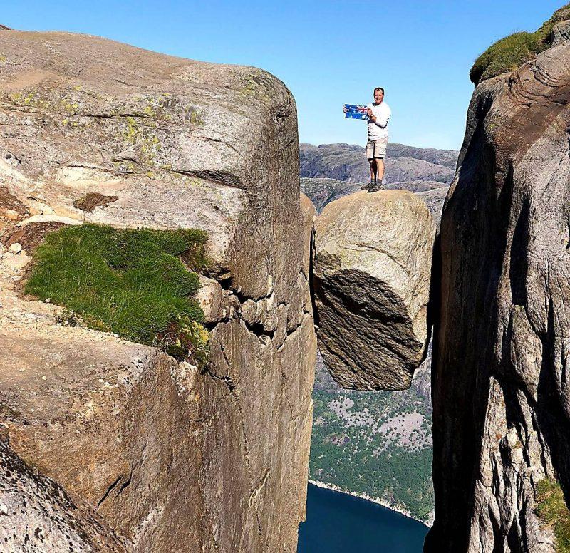 Lars stood on the Kjeragbolten boulder holding a small Australian flag.