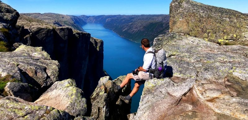 Lars perched on the edge of a rock looking out on to the dark blue fjord