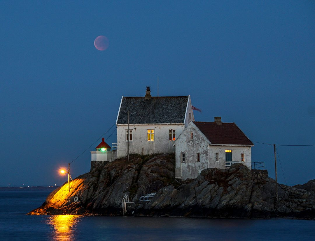 pale outline of blood moon photographed above a lighthouse