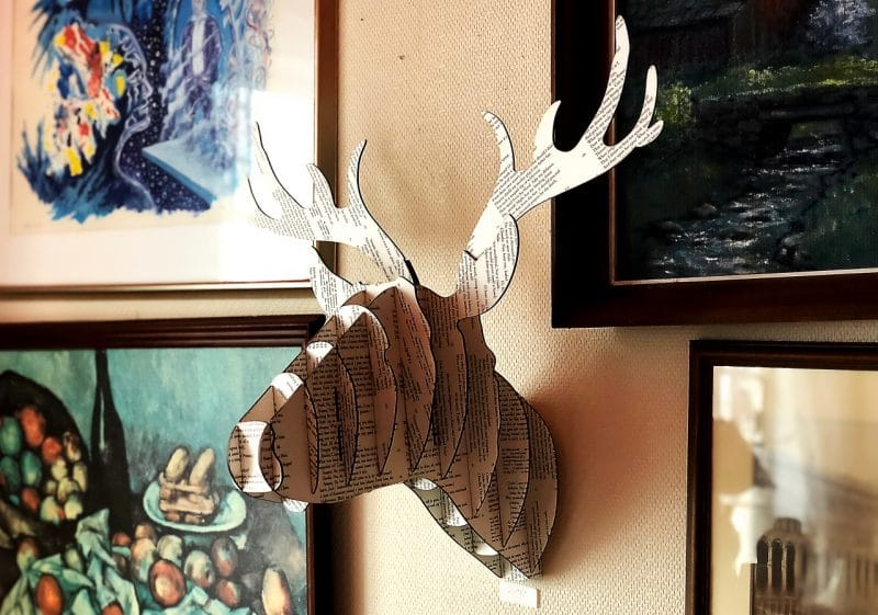 a deer head made of printed on cardboard attached to the wall between 4 paintings.