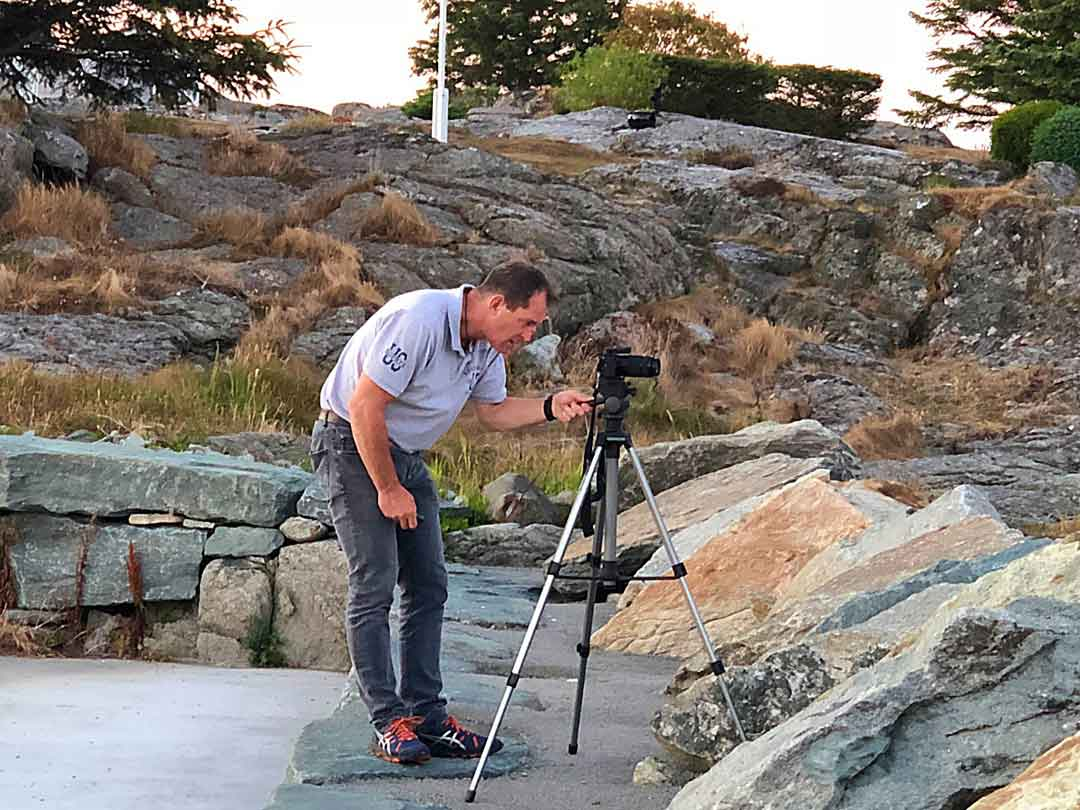 Man looking through camera on tripod