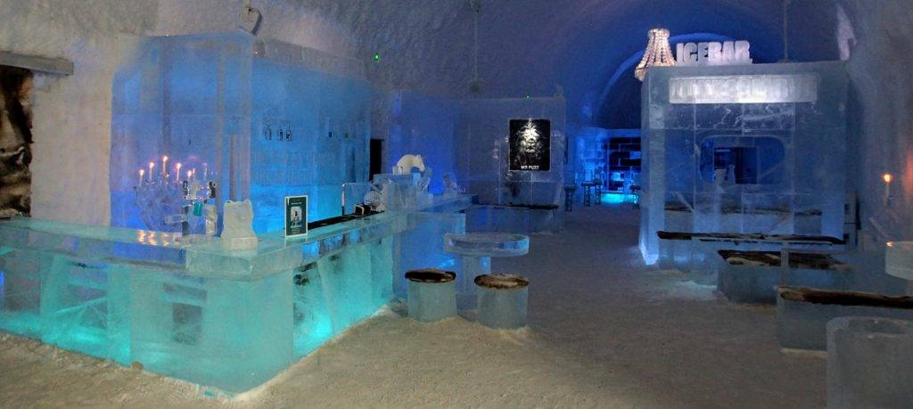 An overview of the main hall of the 365 Ice Hotel - On the left is the serving bar backlit in blue with small ice stools covered in reindeer fur