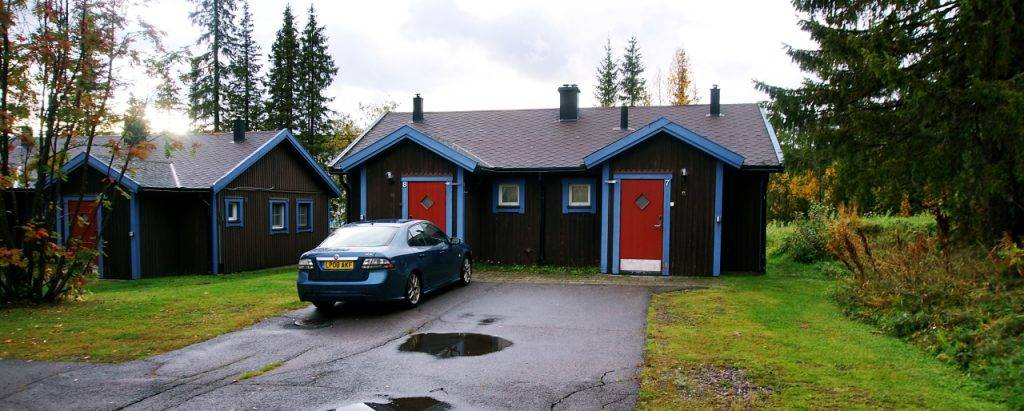 A brown semi detached cabin with a bright red door and blue framed gutters.