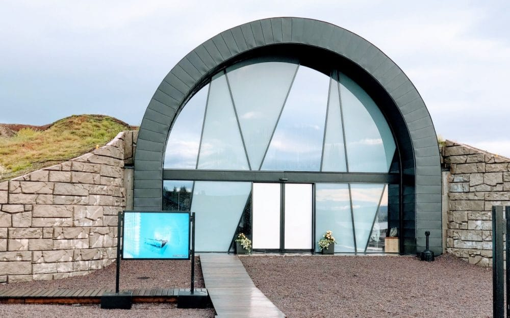A grey arched wall with reflective glass panels is the entrance way to the Ice hotel. Either side is a wall coming to about half the height of the entrance.