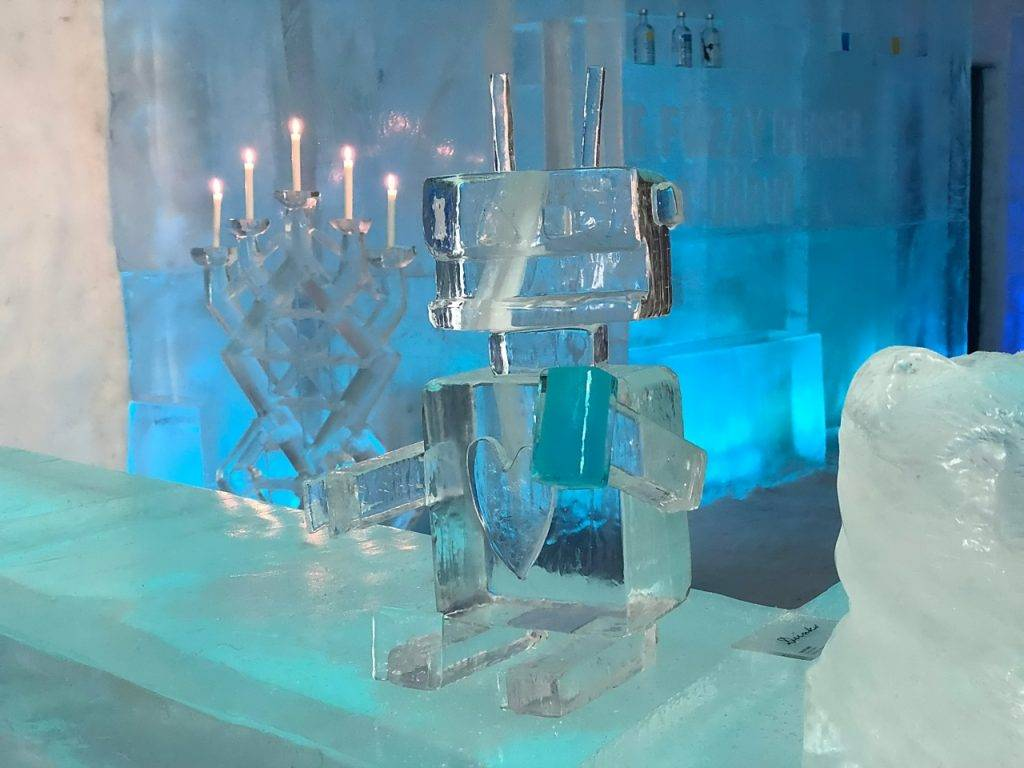 A small ice robot with a heart carved where a heart would be. The ice candelabra is in the background