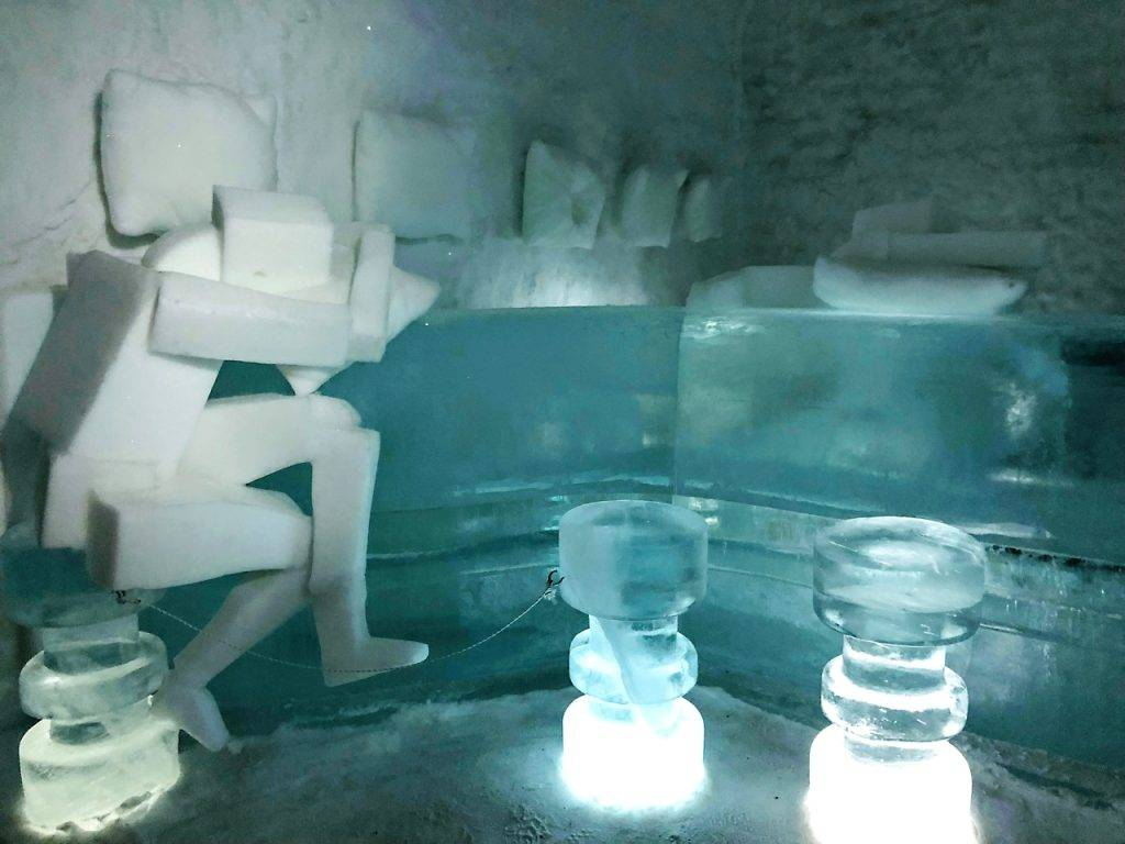 An ice room with a figure carved from ice holding a pillow. Pillow shapes on wall made of ice