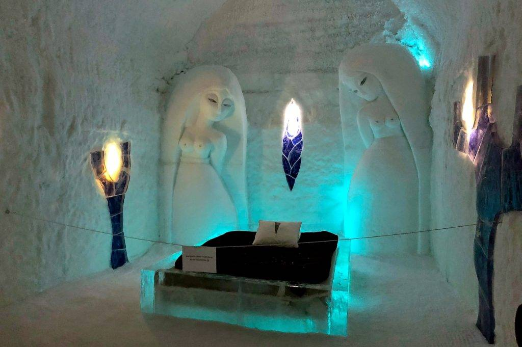 Two carved ice angels overlooking the bed in the middle with blue ice murals on the wall