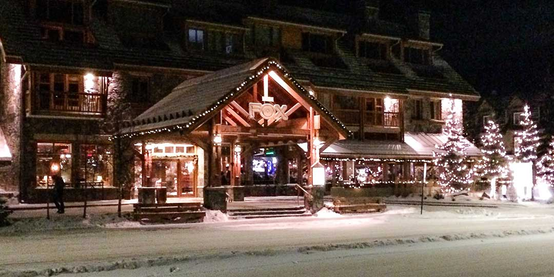 A hotel with sloping roof. outside are four christmas trees lit with white fairy lights. It is nightime and there is snow on the road.
