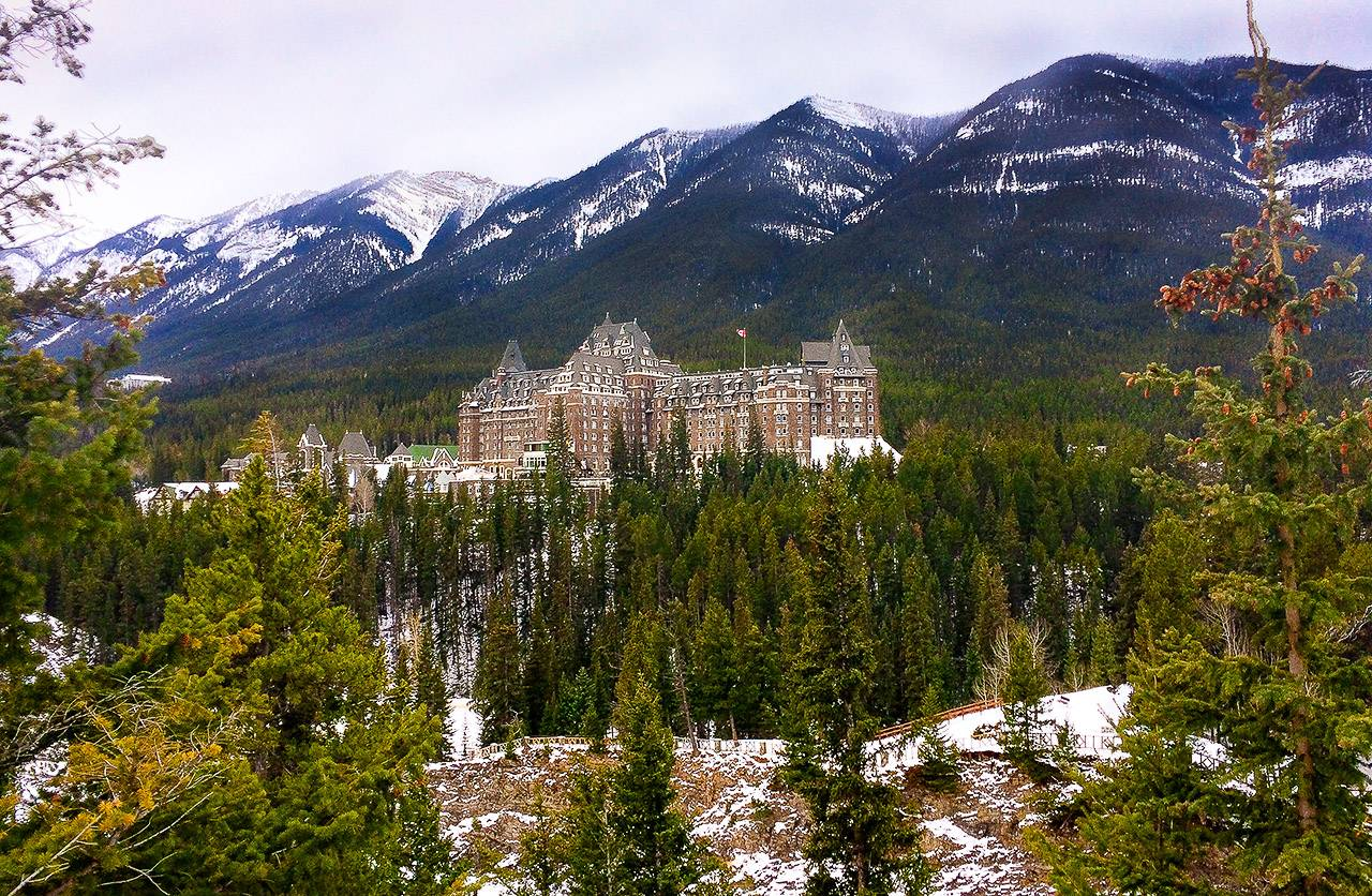Mountains in the background, pine trees in the foreground and in the centre of the photo is a very large hotel - the Fairmont Springs Banff. It is brown and has steeple like roof.