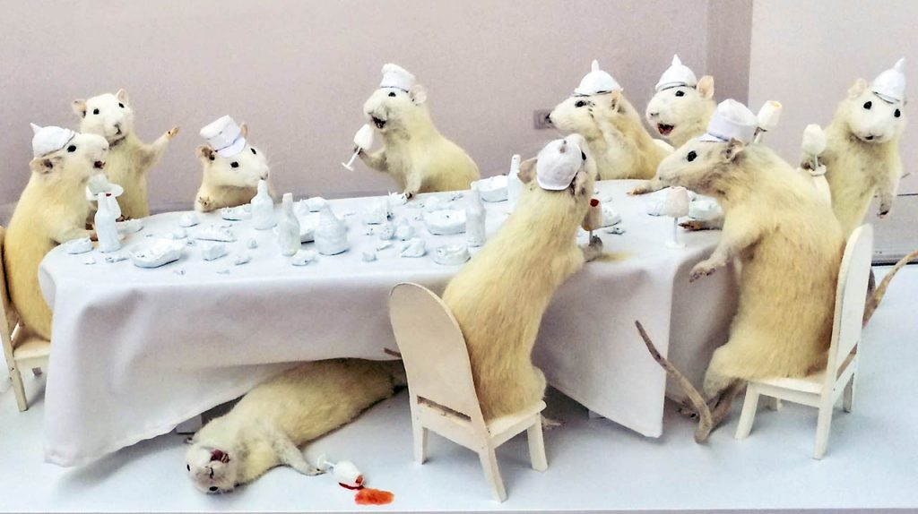 An art instalation at the National Art Gallery of Tirana, Albania. 10 stuffed white dwarf hamsters in poses around a white table that is sized relative to them.