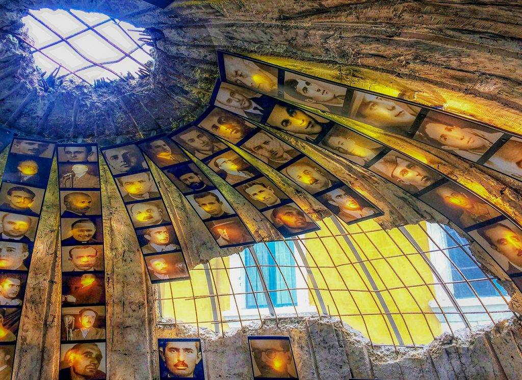 A dome shaped bunker with photographs of men arranged vertically around the dome. There is damage to the outside, so you can see through to the yellow wall of the building outside.