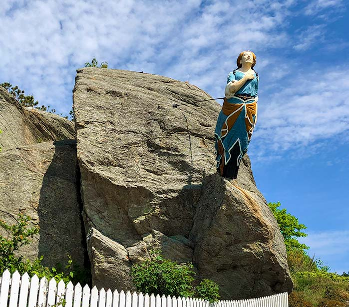 The boat figurehead of a woman attached to the rock at the entrance to Skudeneshavn Park
