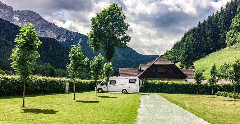 Motorhome parked in a campsite in Slovenia with mountains in backdrop