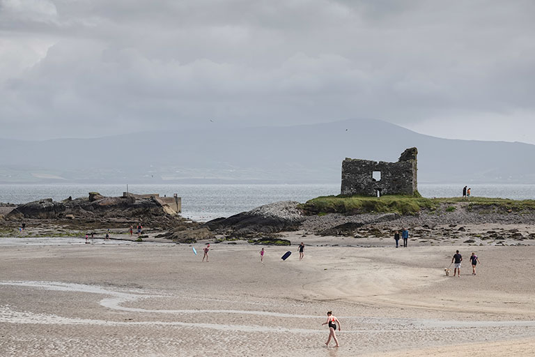 A view of a ruined castle on a beach promontory