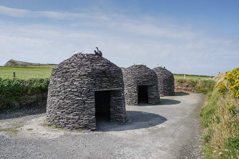 Three rounded stone huts made from flat pieces of stone laid on top of each other