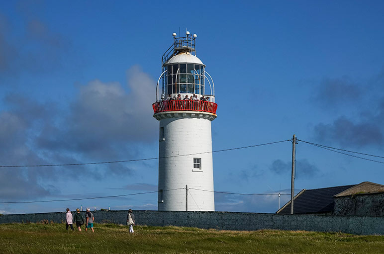 White lighthouse with people on the balcony