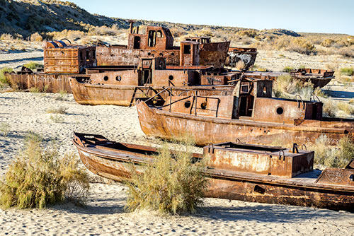 Rusty hulled ships on sandy ground
