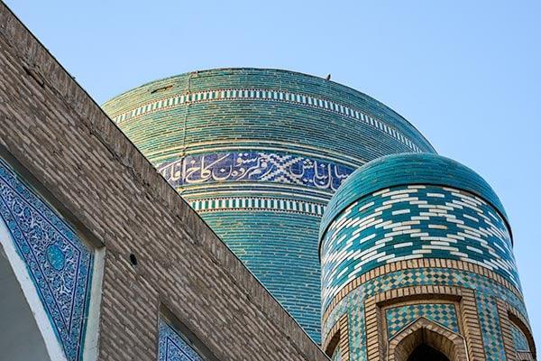 Beautiful tiled mosaics of a madrasah and minaret in Uzbekistan