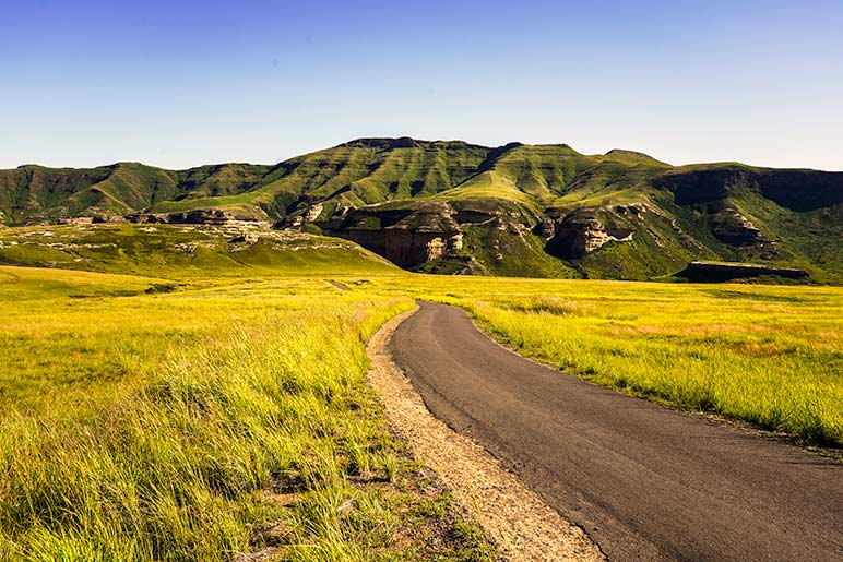 Single lane road in South Africa - road surrounded by green mountains