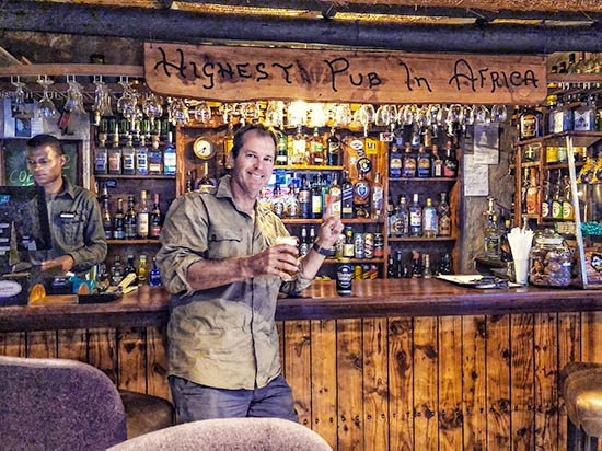 Man having a beer at the highest pub in africa at sani pass