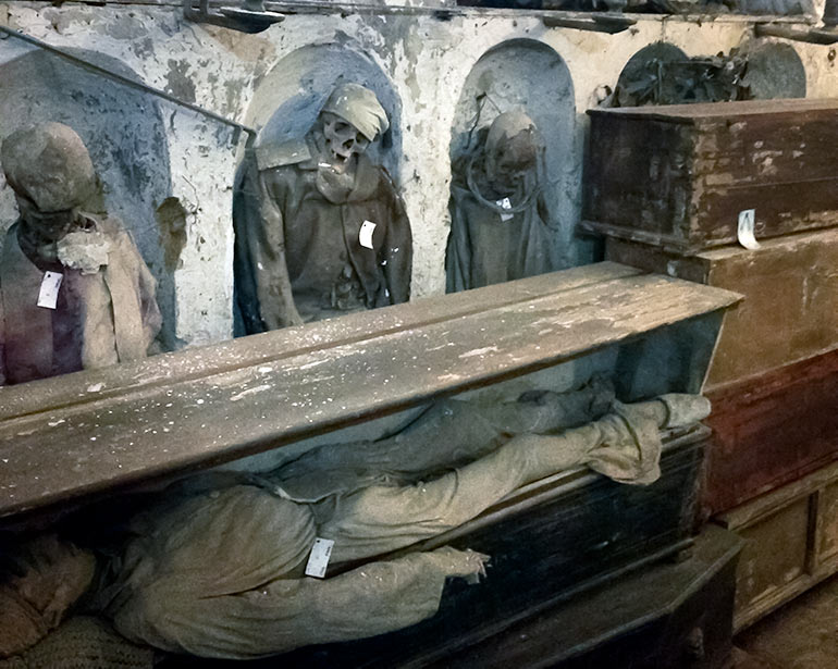 Palermo Catacombs with corpses stood in arches and some laid horizontally in wooden boxes