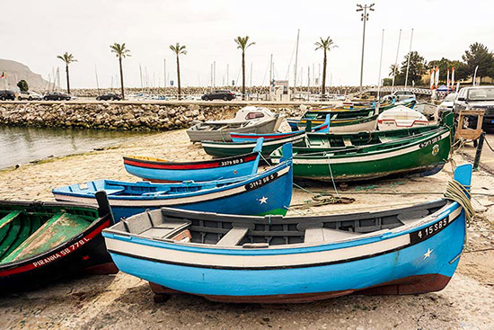 Sesimbra's bright coloured fishing boats beached at the harbour