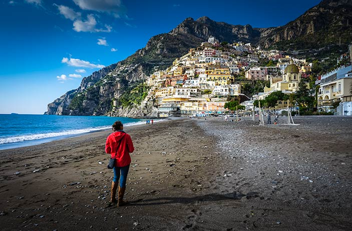 Walking along the empty beach looking towards the town of Positano on the hill