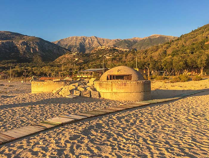 Albanian beach at sunset with a bunker facing at to sea