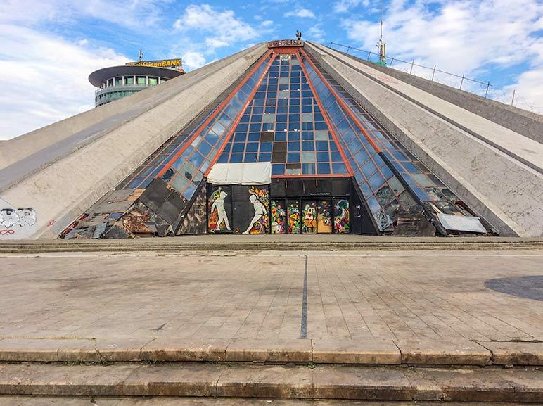 pyramid shaped building in Tirana with graffiti on it