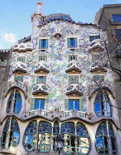 Gaudi designed building in Barcelona - blue and purple with balconies shaped like masks.