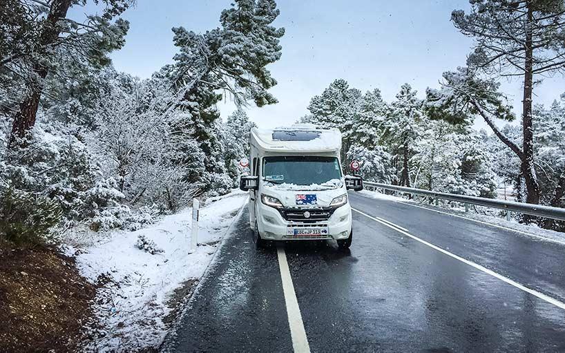 Campervan covered in snow on Spain road Trip