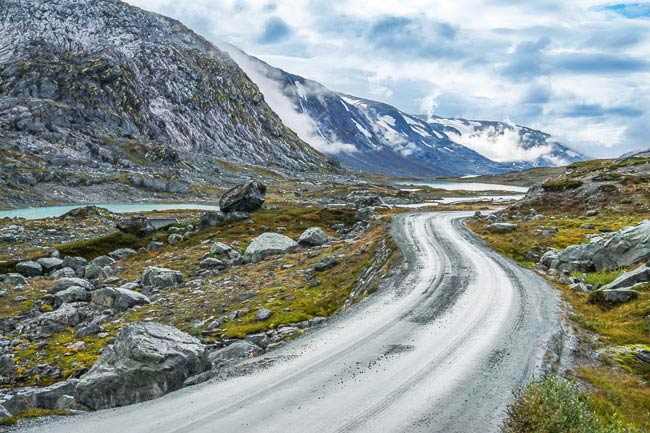 gravel road amongst snowy mountains