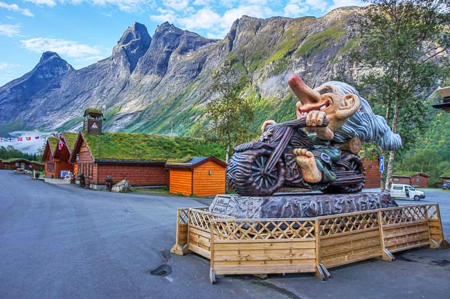 troll on a motobike sculpture with mountains in the background