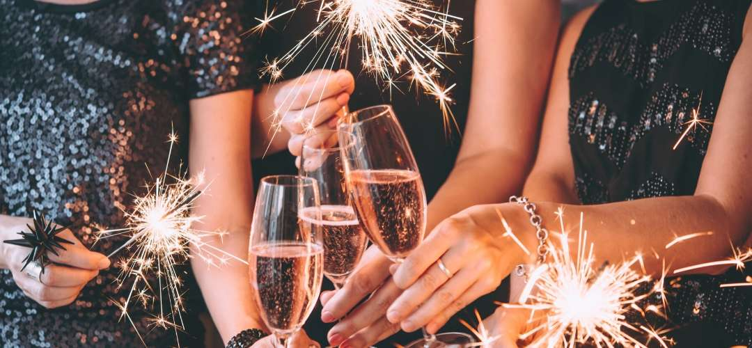 sparklers and women dressed in sparkly black dresses