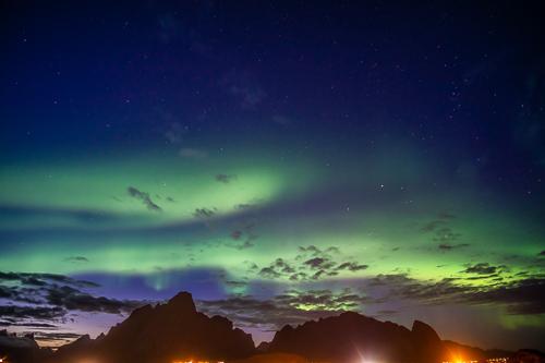 northern lights over dark mountains