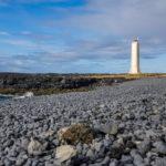 walk along the stony beach towards a lighthouse, iceland