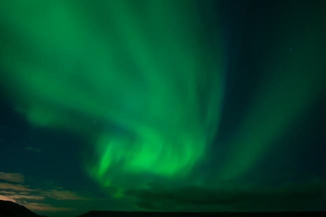 Visiting Iceland in September and seeing green northern lights swirling in the night sky