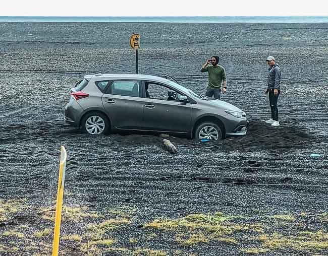 bogged car on an Icelandic volcanic sand beach