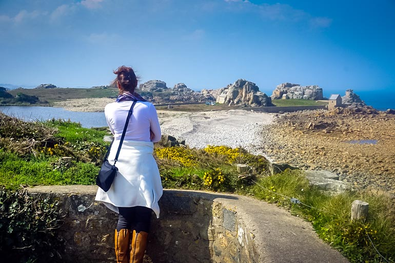 Shelley looking out at a house between rocks in France